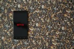 Netflix-Logo auf Smartphone auf Hintergrund von kleinen Steinen Lizenzfreie Stockfotos