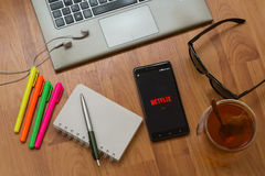 Netflix. Nitra, Slovakia, april 3, 2017: Netflix application in a mobile phone screen. Workplace with a laptop, an earphones, notepad, pen, tea, sunglasses and stock image