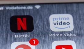 Netflix and Prime Video apps on broken iPhone screen. BERLIN, GERMANY - OCTOBER 15, 2018: Netflix and Prime Video, competing streaming apps on screen of an stock photography