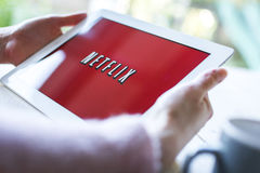 Netflix on tablet pc. Woman hands holding iPad or tablet pc showing Netflix logo on red background royalty free stock photography