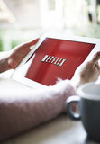 Netflix. Woman hands holding iPad or tablet pc showing Netflix logo on red background royalty free stock images
