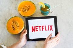 Netflixembleem dat op het slim telefoonscherm wordt getoond met vers fruit Stock Afbeelding