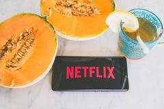 Netflixembleem op een smartphone op een marmeren lijst met vers fruit en drank wordt getoond die Royalty-vrije Stock Afbeelding