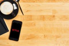 Netflixembleem op zwarte Apple-iPhone en zwarte kop van koffie of cappuccino op houten lijst stock afbeeldingen