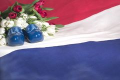 The Netherlands. A dutch flag, red & white tulips and blue wooden shoes royalty free stock images