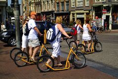 Netherlands, Amsterdam, mode of transport. Amsterdam, Netherlands - June 13th 2006: unidentified tourists on kind of kick scooters in a street in Amsterdam stock image