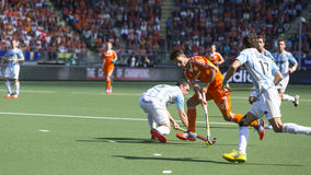 Netherlands beats Argentinia during the Hockey World Cup 2014. THE HAGUE, NETHERLANDS - JUNE 1: Dutch player Kemperman is playing the ball surrounded by stock images