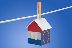 Netherlands, dutch and EU flag on paper house. Concept - Netherlands, dutch and EU flag painted on a paper house hanging on a rope Royalty Free Stock Photography