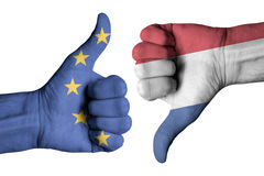 Netherlands and Europe flag on human male thumb up and down hand. Netherlands and Europe flag on human male thumb up and down  hands Royalty Free Stock Photo