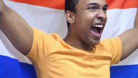 Netherlands Fan celebrating while holding the flag of Netherlands in Slow Motion. High quality stock photography