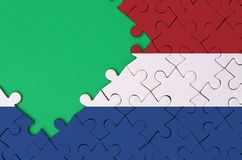 Netherlands flag is depicted on a completed jigsaw puzzle with free green copy space on the left side.  royalty free stock photo