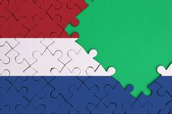 Netherlands flag is depicted on a completed jigsaw puzzle with free green copy space on the right side.  royalty free illustration