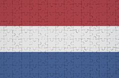 Netherlands flag is depicted on a folded puzzle stock image