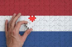 Netherlands flag is depicted on a puzzle, which the man`s hand completes to fold.  stock photography