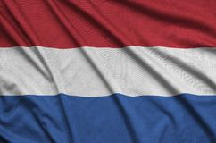 Netherlands flag is depicted on a sports cloth fabric with many folds. Sport team banner. Netherlands flag is depicted on a sports cloth fabric with many folds royalty free stock photo