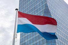 Netherlands flag on a pole waving, modern office building background. Netherlands flag. Dutch flag on a pole waving, modern office building background royalty free stock photos