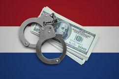 Netherlands flag with handcuffs and a bundle of dollars. Currency corruption in the country. Financial crimes.  stock photo