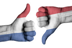 Netherlands flag on human male thumb up and down hands Stock Photos