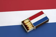 Netherlands flag is shown in an open matchbox, which is filled with matches and lies on a large flag.  royalty free stock photography