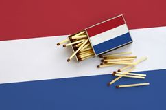Netherlands flag is shown on an open matchbox, from which several matches fall and lies on a large flag.  stock photo