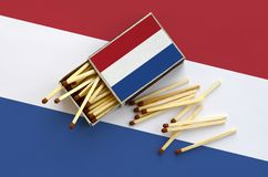 Netherlands flag is shown on an open matchbox, from which several matches fall and lies on a large flag.  stock photography