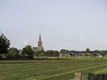 Netherlands landscape, looking at the village of Schalkwijk. A view of the chruch tower in Schalkwijk and the surrounding farmlands. Schalkwijk is a little royalty free stock photos