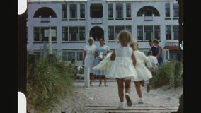 Twins running from the beach. Netherlands, Noordwijk, Summer 1956. Two shot sequence of two little blond female twins dressed in white running from the beach to stock video footage