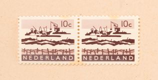 THE NETHERLANDS 1970: A stamp printed in the Netherlands shows the construction of the afsluitdijk, circa 1970. A stamp printed in the Netherlands shows the stock images