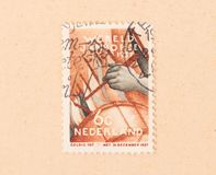 A stamp printed in the Netherlands shows someone playing the drums, circa 1950. THE NETHERLANDS 1950: A stamp printed in the Netherlands shows someone playing stock photos
