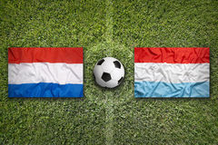 Netherlands vs. Luxembourg flags on soccer field Stock Photography