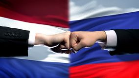 Netherlands vs Russia conflict international relations, fists on flag background. Stock photo stock photo