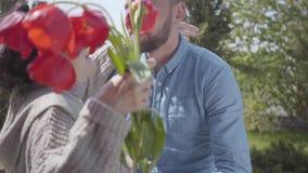 Neto considerável que visita sua avó, trazendo seu ramalhete das tulipas O homem farpado que abra?a sua av? Povos vídeos de arquivo