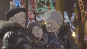 Neto idoso feliz entusiasmado do menino do neto do abraço da avó do casal na noite festiva da iluminação da luz de Natal filme
