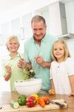 Netos que ajudam o avô a preparar a salada Imagens de Stock Royalty Free