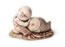 Netsuke du garçon avec de grands poissons D'isolement Un sculptur miniature Images libres de droits