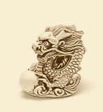 Netsuke of east dragon, which guarding the egg. Isolated. Netsuke of east dragon, which guarding the egg. A miniature sculpture, which was used as a button-like Royalty Free Stock Photography