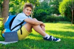 Nett, intelligent, sitzt Junge im blauen Hemd auf dem Gras nahe bei seinem Schulrucksack, Kugel, Tafel, Arbeitsbücher Ausbildung lizenzfreie stockbilder