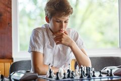 Nett, intelligent, spielt Junge im weißen Hemd Schach auf dem Schachbrett im Klassenzimmer Ausbildung, Hobby, Training stockfotos