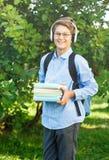 Nett, Junge in den runden Gläsern und blaues Hemd hält Bücher mit seinen Händen im Park Lese-und Lernkonzeptausbildung stockfotos