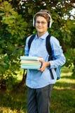 Nett, Junge in den runden Gläsern und blaues Hemd hält Bücher mit seinen Händen im Park Lese-und Lernkonzeptausbildung, stockfotografie