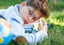 Nett, Junge in den runden Gläsern und blaues Hemd liest Buch auf dem Gras im Park Bildung, zurück zu Schule lizenzfreies stockfoto