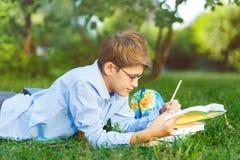 Nett, Junge in den runden Gläsern und blaues Hemd liest Buch auf dem Gras im Park Bildung, zurück zu Schule lizenzfreies stockbild