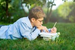 Nett, Junge in den runden Gläsern und blaues Hemd liest das Buch, das auf dem Gras im Park liegt Bildung, zurück zu Schule lizenzfreie stockbilder