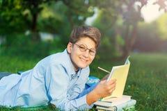 Nett, Junge in den runden Gläsern und blaues Hemd liest das Buch, das auf dem Gras im Park liegt Bildung, zurück zu Schule stockfoto
