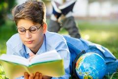 Nett, Junge in den runden Gläsern und blaues Hemd liest das Buch, das auf dem Gras im Park liegt Bildung, zurück zu Schule stockfotografie