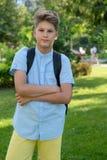 Nett, Junge im blauen Hemd mit Rucksack und Arbeitsbücher in seinen Händen vor seiner Schule Bildung, zurück zu Schule lizenzfreie stockfotografie