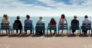 Nett - Leute sitzen auf Stühlen Stockbild