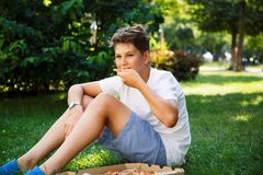 Nett, sitzt Junge im weißen T-Shirt auf dem Gras und nimmt eine Scheibe der Pizza im Park stockfoto