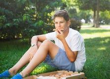 Nett, sitzt Junge im weißen T-Shirt auf dem Gras und nimmt eine Scheibe der Pizza im Park stockbild