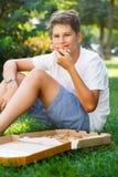 Nett, sitzt Junge im weißen T-Shirt auf dem Gras und nimmt eine Scheibe der Pizza im Sommerpark Junge isst Pizza lizenzfreie stockfotografie